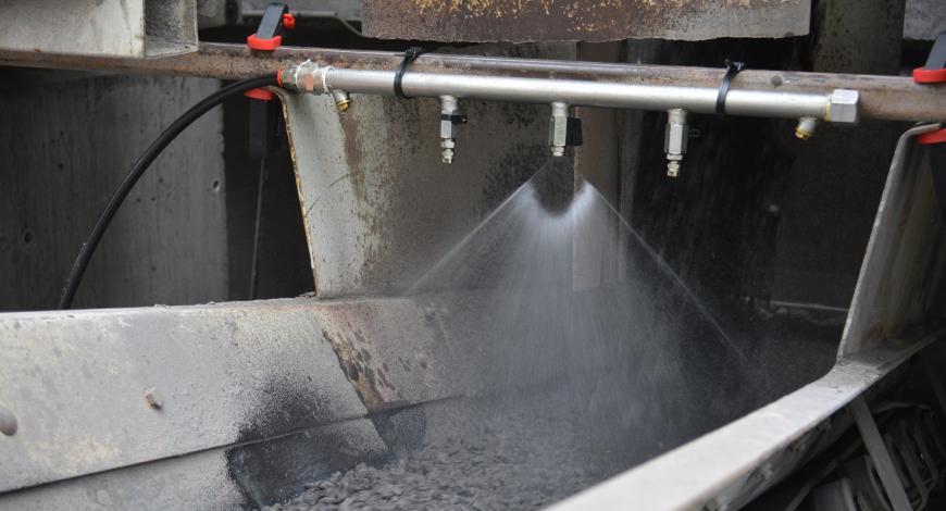 Ajout de produit régénérant aux AE sur le tapis convoyeur à l'aide d'un dispositif de pulvérisation.