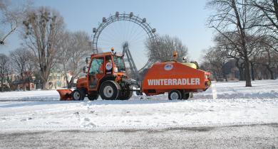 Winterradler : tracteur et sa remorque épandeuse de saumure lors de l'entretien d'une piste cyclable.